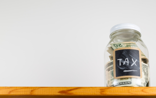 Single glass jar with chalk labels used for saving US dollar bills and notes for tax and taxes